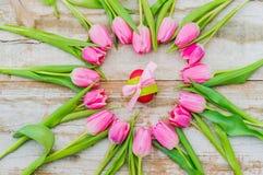 Счастливая предпосылка пасхи с розовыми цветками тюльпанов и пасхальным яйцом Стоковое Фото