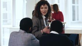 Счастливая привлекательная молодая бизнес-леди руководителя давая направления африканским мужским менеджерам на современном удобн сток-видео