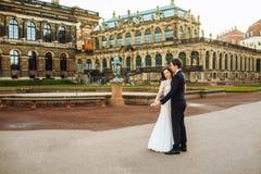 Счастливая роскошная пара свадьбы стоящ и целующ в улицах старого города Стоковые Изображения RF