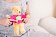 Счастливая рука беременной женщины держа куклу плюшевого медвежонка на ее животе w Стоковая Фотография