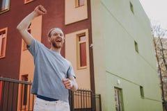 Счастливая рука удерживания молодого человека вверх как победитель стоковое фото