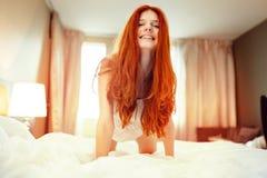 Счастливая сексуальная женщина redhead на кровати стоковые изображения