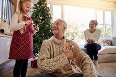 Счастливая семья аранжируя света рождества и имея потеху Стоковое Изображение RF