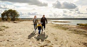 Счастливая семья бежать вдоль пляжа осени стоковое изображение
