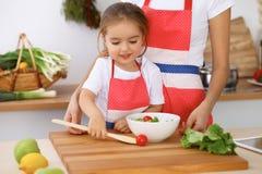 Счастливая семья в кухне Дочь матери и ребенка варя вкусное breakfest свежего салата Маленький отрезать хелпера Стоковые Изображения RF