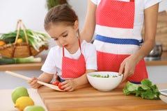 Счастливая семья в кухне Дочь матери и ребенка варя вкусное breakfest свежего салата Маленький отрезать хелпера Стоковая Фотография RF