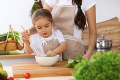 Счастливая семья в кухне Дочь матери и ребенка варя вкусное breakfest свежего салата Маленький отрезать хелпера Стоковые Изображения