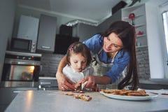 Счастливая семья в кухне Концепция еды праздника Мать и дочь украшают печенья Счастливая семья в делать домодельный Стоковое Изображение