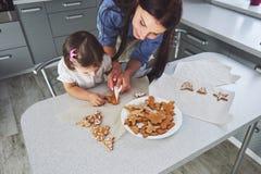 Счастливая семья в кухне Концепция еды праздника Мать и дочь украшают печенья Счастливая семья в делать домодельный Стоковые Изображения