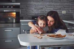 Счастливая семья в кухне Концепция еды праздника Мать и дочь украшают печенья Счастливая семья в делать домодельный Стоковое Изображение RF