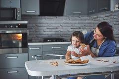 Счастливая семья в кухне Концепция еды праздника Мать и дочь украшают печенья Счастливая семья в делать домодельный Стоковое Фото