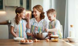 Счастливая семья в кухне мать и дети подготавливая тесто, пекут печенья стоковые изображения rf