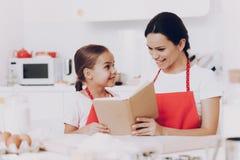 Счастливая семья в кухне печет и прочитала книгу стоковые изображения rf