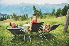 Счастливая семья в швейцарце Альпах, наслаждаясь изумительным взглядом, перемещение с детьми Стоковые Фотографии RF