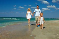Счастливая семья гуляя на пляж моря, каникулу стоковое фото rf