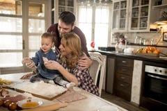 Счастливая семья делая макаронные изделия в кухне дома Стоковые Изображения