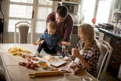 Счастливая семья делая макаронные изделия в кухне дома Стоковые Фото