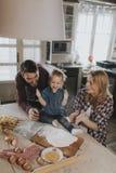 Счастливая семья делая макаронные изделия в кухне дома Стоковая Фотография RF