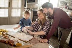 Счастливая семья делая макаронные изделия в кухне дома Стоковые Фотографии RF