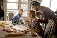 Счастливая семья делая макаронные изделия в кухне дома Стоковая Фотография
