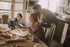 Счастливая семья делая макаронные изделия в кухне дома Стоковое Фото
