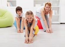 Счастливая семья делая протягивать работает на дому стоковое фото rf