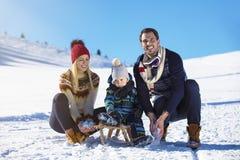 Счастливая семья едет розвальни в древесине зимы, жизнерадостных развлечениях зимы Стоковые Изображения
