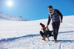 Счастливая семья едет розвальни в древесине зимы, жизнерадостных развлечениях зимы Стоковые Фотографии RF