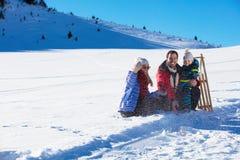 Счастливая семья едет розвальни в древесине зимы, жизнерадостных развлечениях зимы Стоковые Изображения RF