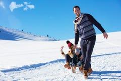 Счастливая семья едет розвальни в древесине зимы, жизнерадостных развлечениях зимы Стоковое Изображение RF