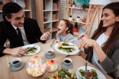 Счастливая семья есть блюда на таблице совместно Родители при их дочь собранная на таблице Стоковые Изображения RF