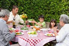 Счастливая семья есть в саде стоковая фотография