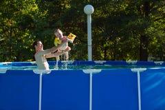 Счастливая семья играя в плавательном бассеине Принципиальная схема каникулы лета Стоковое Изображение