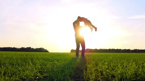 Счастливая семья играя природу в парке на заходе солнца Отец держит его сына оружиями и поворачивает с ним в медленном