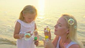 Счастливая семья играя пузыри мыла острословия внешние на пляже во время отпуска красивого захода солнца счастливого в замедленно акции видеоматериалы