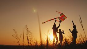 Счастливая семья играя с змеем на заходе солнца Мама, папа и дочь счастливы совместно Стоковые Изображения RF