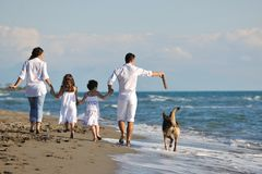 Счастливая семья играя с собакой на пляже Стоковая Фотография