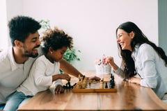 Счастливая семья играя шахмат совместно дома Стоковая Фотография RF