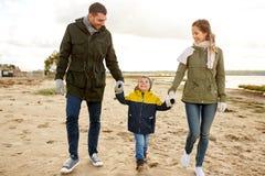 Счастливая семья идя вдоль пляжа осени стоковое фото