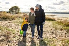 Счастливая семья идя вдоль пляжа осени стоковое изображение