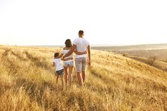 Счастливая семья идя в природу на заходе солнца летом стоковое изображение