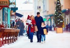Счастливая семья идя совместно на снежную улицу города во время зимы Стоковая Фотография