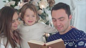 Счастливая семья из трех человек читая совместно на вечере рождества Стоковое Изображение