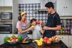 Счастливая семья имеет папы, мамы и их маленькой дочери варя совместно в кухне стоковая фотография rf