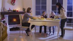 Счастливая семья имеет праздничный обедающий на таблице рождества видеоматериал