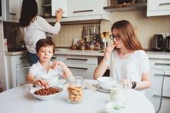 Счастливая семья имея завтрак дома Мать при 2 дет есть в утре в современной белой кухне Стоковая Фотография