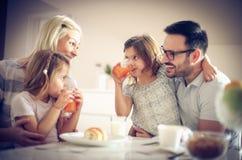 Счастливая семья имея завтрак стоковая фотография