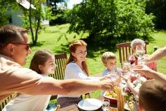 Счастливая семья имея обедающий или прием гостей в саду лета стоковое изображение rf