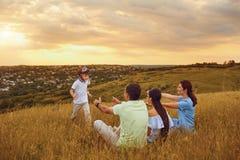 Счастливая семья имея потеху играя на траве в природе Стоковые Изображения RF