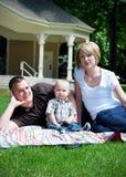 Счастливая семья лежа в траве - вертикали Стоковые Изображения RF